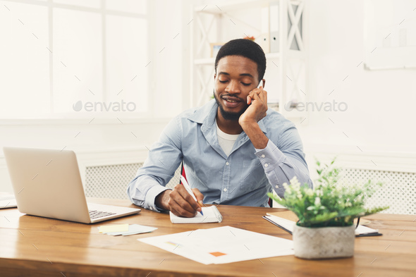 Young black businessman talking on mobile phone - Stock Photo - Images