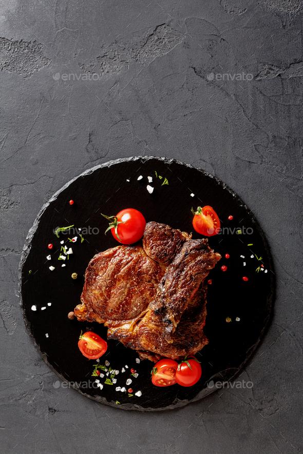 Rare rib eye steak on dark plate, top view - Stock Photo - Images