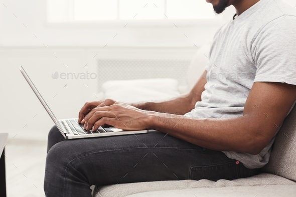 Closeup of young man working on laptop - Stock Photo - Images