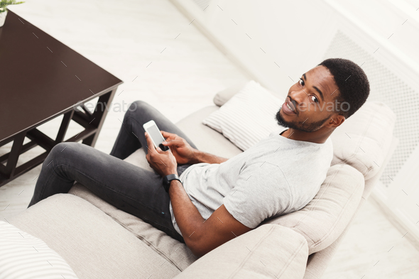 Happy young man at home messaging on mobile - Stock Photo - Images