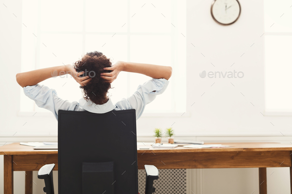 Business woman resting in office with hands behind her head - Stock Photo - Images