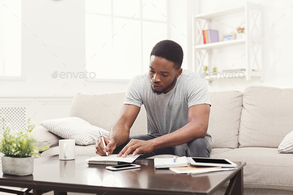 Concentrated young man preparing for exams at home - Stock Photo - Images