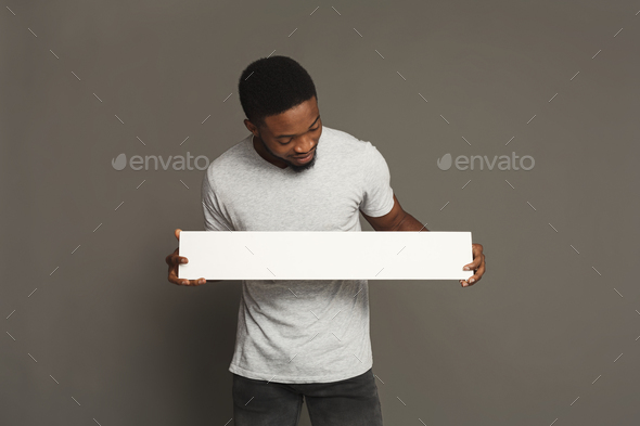 Picture of young african-american man holding white blank board - Stock Photo - Images