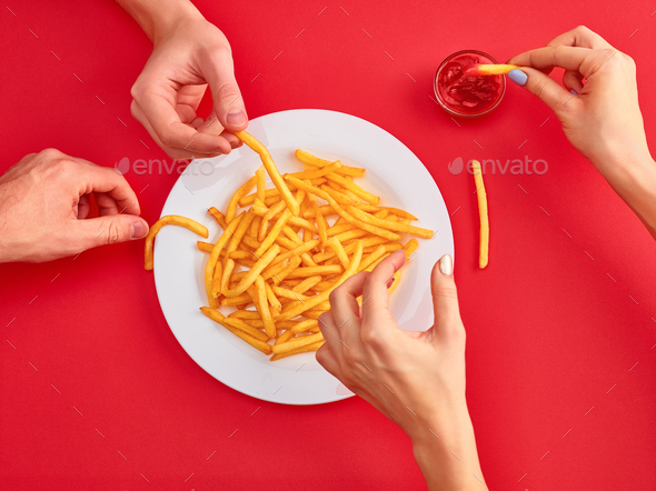 Young woman eating french fries potato with ketchup in a restaurant - Stock Photo - Images
