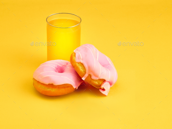 The donuts and fresh orange juice on yellow background - Stock Photo - Images
