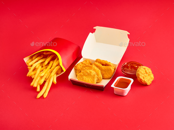 chicken nuggets and french fries on red background - Stock Photo - Images