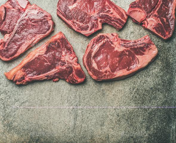 Porterhouse, t-bone and rib-eye steaks over grey background - Stock Photo - Images