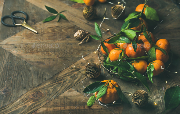 Fresh tangerines, decoration toys and light garland over rustic background - Stock Photo - Images