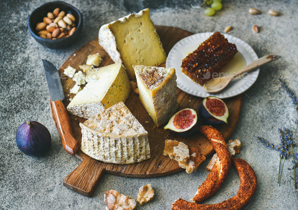 Cheese assortment, figs, honey, freshly baked bread and nuts - Stock Photo - Images