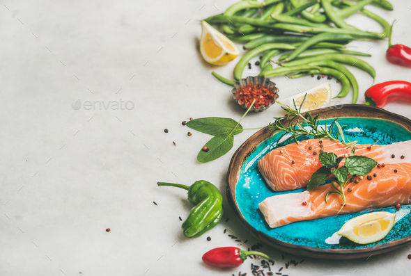 Raw salmon steaks with vegetables, greens, rice in blue plate - Stock Photo - Images