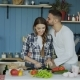 Happy Young Couple in the Kitchen. Attractive Dancing Woman Cooking and Feeding Her Boyfriend in the - VideoHive Item for Sale
