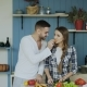 Happy Young Couple in the Kitchen. Attractive Dancing Man Feeding His Girlfriend While She Is - VideoHive Item for Sale