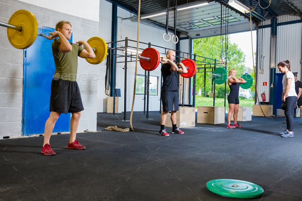 Team training with weights and kettlebells at fitness gym - Stock Photo - Images