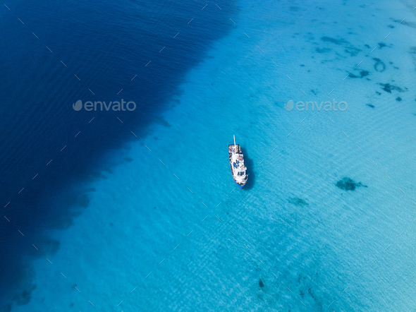 Aerial view of ship floating over crystal clear waters of Grand - Stock Photo - Images