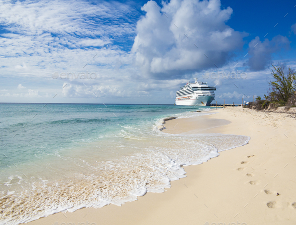 A cruise ship docks in Grand Turk with waves and sand in the for - Stock Photo - Images