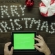 Adult Man Uses Tablet Pc with Green Screen By Christmas Decorated Desk, Top Down Shot - VideoHive Item for Sale