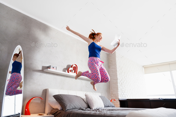 Good News For Happy Young Woman Girl Jumping On Bed - Stock Photo - Images