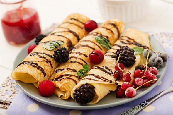 Pancakes with chocolate, jam and berries. Tasty breakfast. - Stock Photo - Images