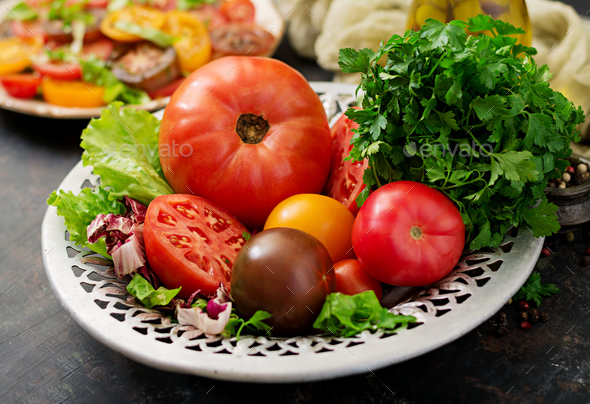 Tomatoes of different colors with green herbs in a bowl on a black background - Stock Photo - Images
