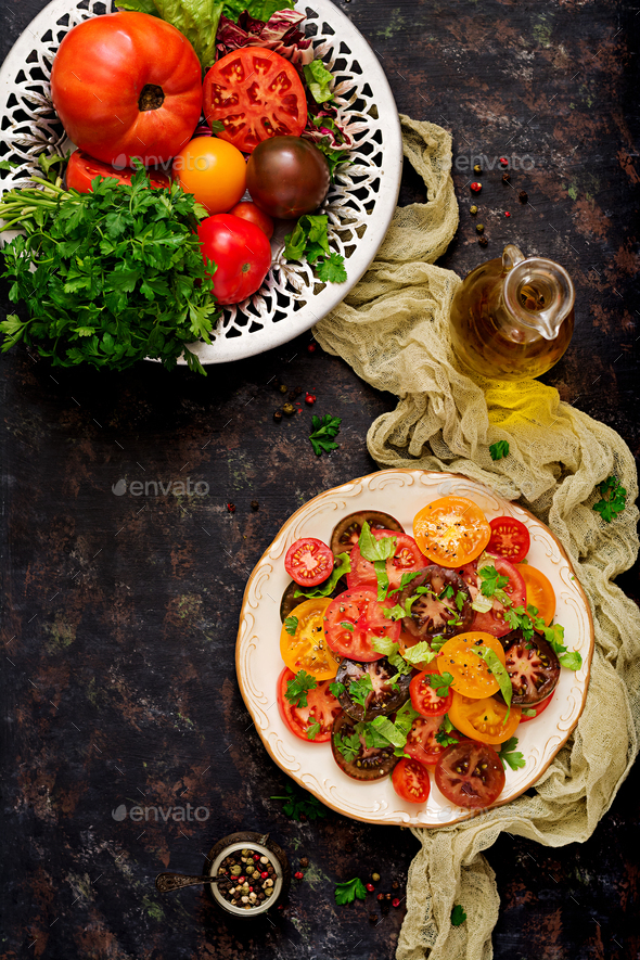 Summer salad of tomatoes of different colors with green herbs and pepper. Top view - Stock Photo - Images