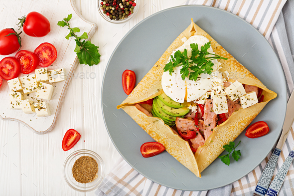 Pancakes with egg poached, feta cheese, fried ham, avocado and tomatoes - Stock Photo - Images
