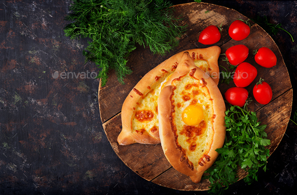 Khachapuri in Adjarian. Open pie with mozzarella and egg. Georgian cuisine. - Stock Photo - Images