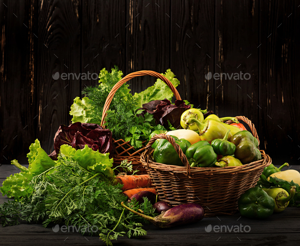 Assortment of vegetables and green herbs. Market. Vegetables in a basket on a dark background - Stock Photo - Images