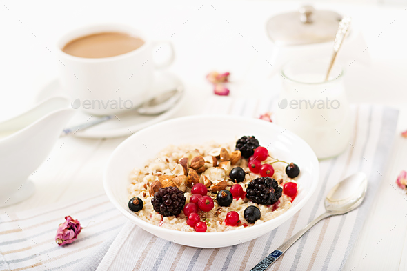 Tasty and healthy oatmeal porridge with berry, flax seeds and nuts.  - Stock Photo - Images