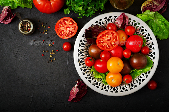 Tomatoes of different colors with green herbs in a bowl on a black background. Flat lay. Top view - Stock Photo - Images
