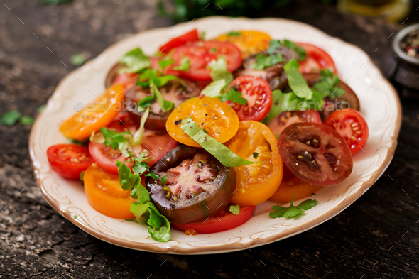 Summer salad of tomatoes of different colors with green herbs and pepper. - Stock Photo - Images