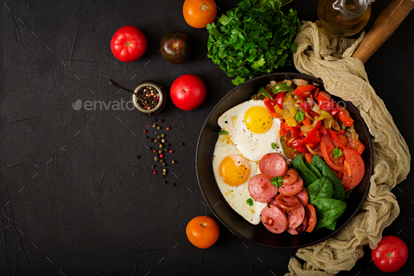 Breakfast. Fried eggs with sausage and vegetables in a frying pan  - Stock Photo - Images