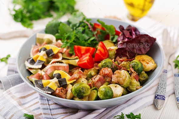 Bowl with Farfalle pasta, Brussels sprouts with bacon and fresh vegetable salad - Stock Photo - Images
