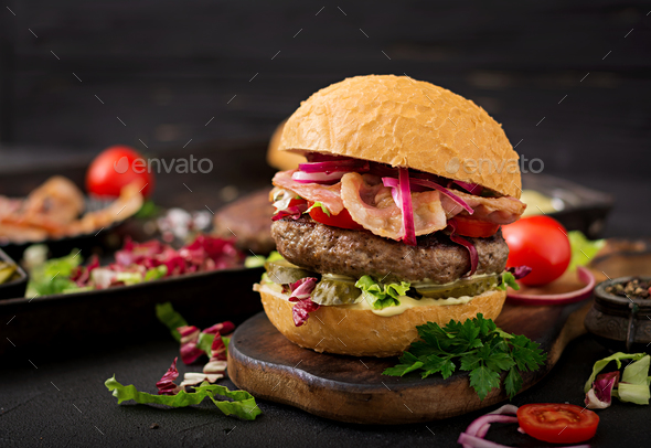 Big sandwich - hamburger burger with beef,  tomato, pickled cucumber and fried bacon - Stock Photo - Images