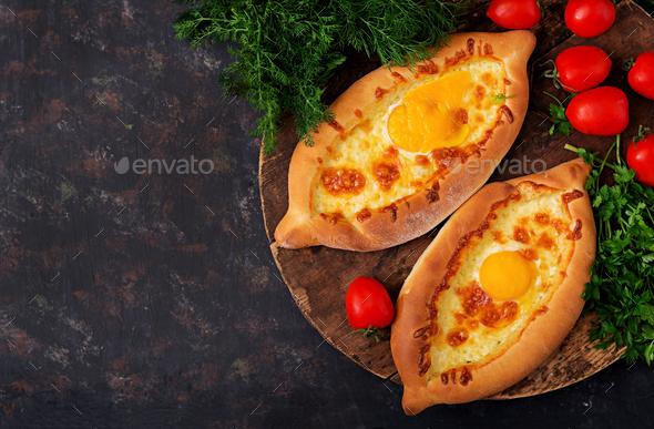 Khachapuri in Adjarian. Open pie with mozzarella and egg. Georgian cuisine. - Stock Photo - Images