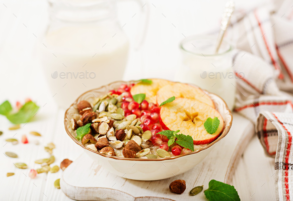 Tasty and healthy oatmeal porridge with apples, pomegranate and nuts - Stock Photo - Images