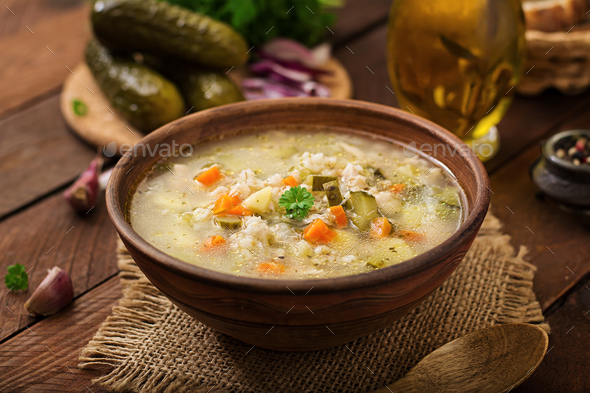 Soup with pickled cucumbers and pearl barley - rassolnik on a wooden background. - Stock Photo - Images
