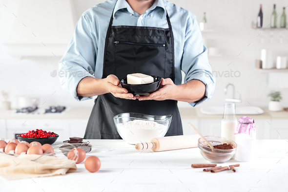 A cook with eggs on a rustic kitchen against the background of men's hands - Stock Photo - Images