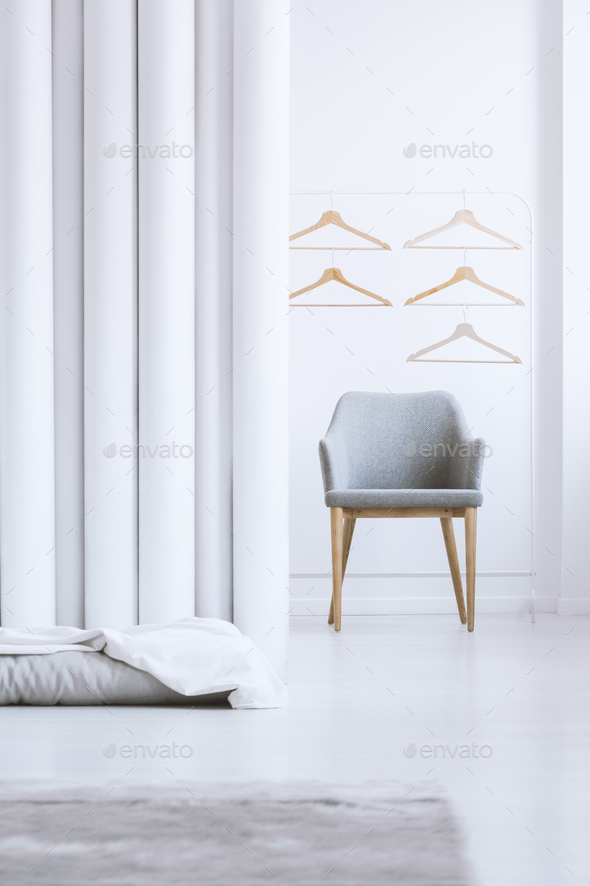 Wooden hangers above gray armchair - Stock Photo - Images