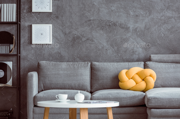 Grey settee against concrete wall - Stock Photo - Images