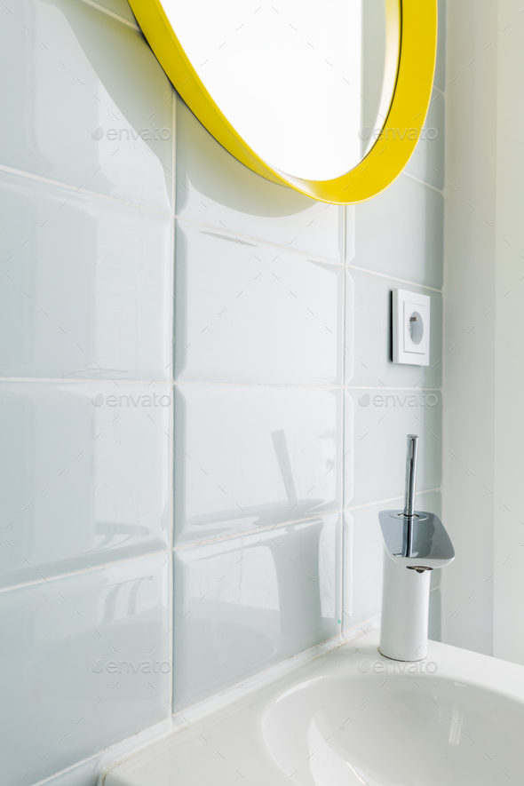 White bathroom with yellow mirror - Stock Photo - Images