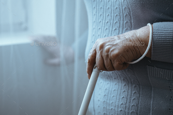 Blind person holding white cane - Stock Photo - Images