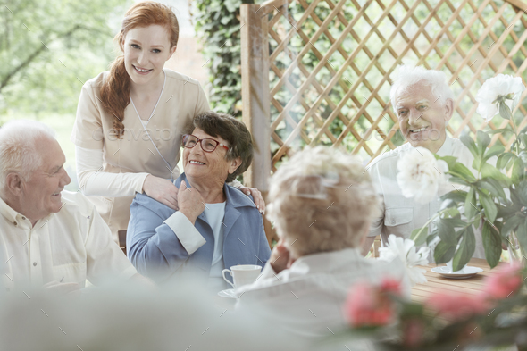 Volunteer supports an older woman - Stock Photo - Images