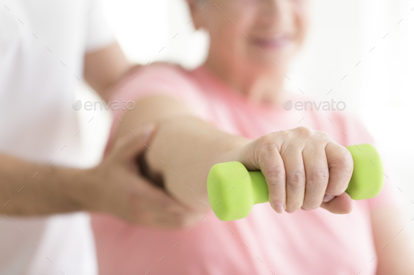 Elderly patient holding minor dumb-bell - Stock Photo - Images