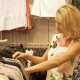The Blonde Girl Chooses Clothes Hanging on the Hangers in the Clothing Shop. - VideoHive Item for Sale