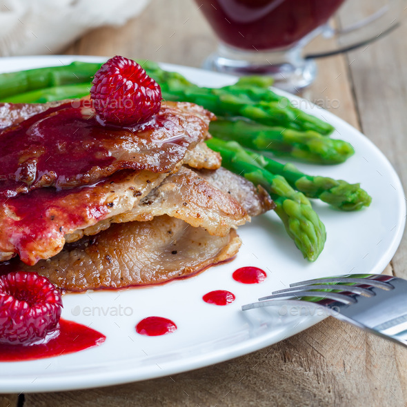 Pork cutlets with raspberry sauce and asparagus on white plate, square - Stock Photo - Images