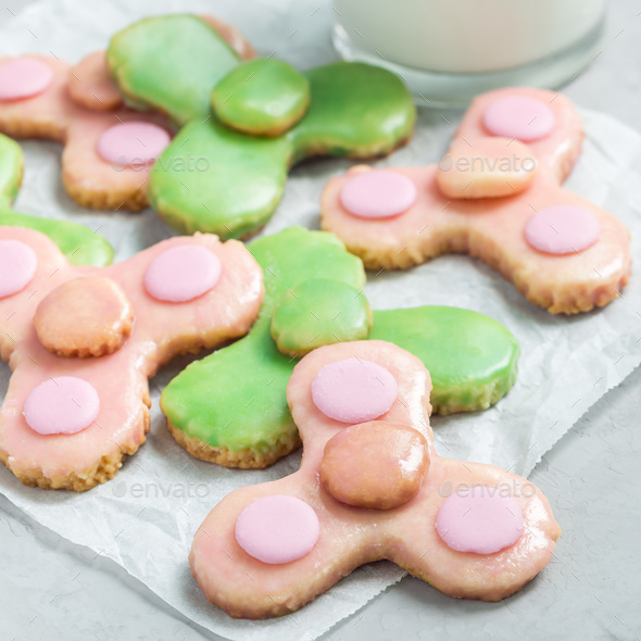 Homemade shortbread cookies made in trendy spinner toy form and a glass of milk, square - Stock Photo - Images