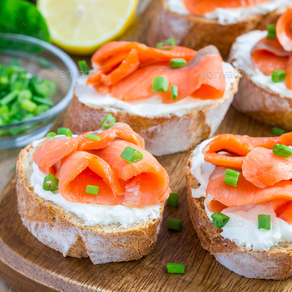 Sandwich with smoked salmon and cream cheese on wooden board, square - Stock Photo - Images