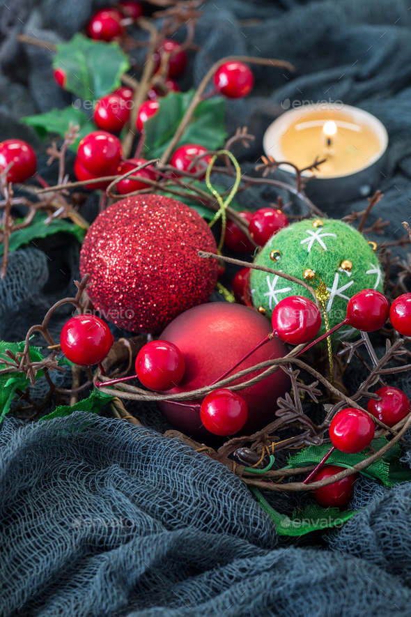 Christmas composition with holly, holiday balls and candle on dark background, vertical, copy space - Stock Photo - Images