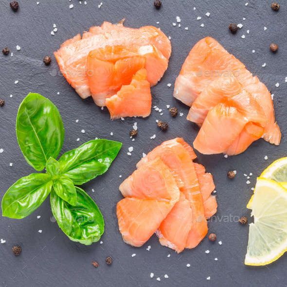 Smoked salmon filet with lemon and basil on gray stone, top view, square format - Stock Photo - Images