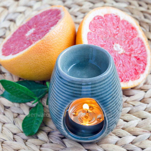Aroma lamp with grapefruit essential oil on woven mat, grapefruits on background, square - Stock Photo - Images